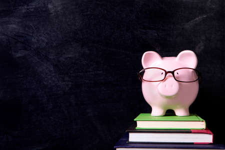 college fund savings: Piggybank with glasses and blackboard