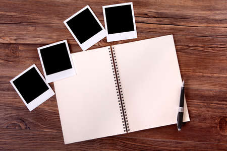 diaries: Photo album on a wood table with several style instant camera photo print frames. Stock Photo