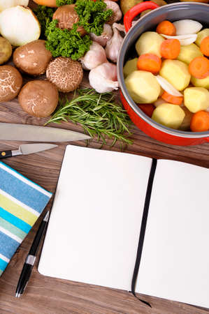 Cook book with vegetables and casserole dish Stock Photo