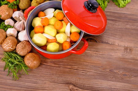 Red casserole dish with winter vegetables and herbs Stock Photo