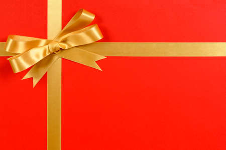 gift ribbon: Gold bow gift ribbon red background Stock Photo