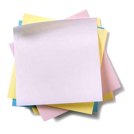 Onordelijke stapel diverse kleuren kleverige postnota's die op wit worden geïsoleerd