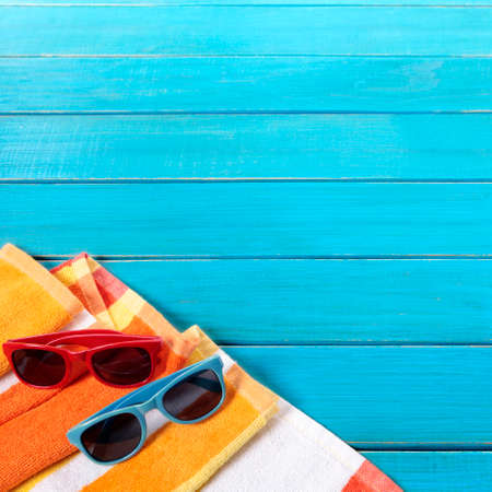 Beach scene with two pairs of sunglasses and orange striped towel on old blue painted wood decking.  Space for copy.