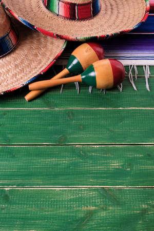 Mexico sombrero border mexican maracas old green wood background vertical Stock Photo