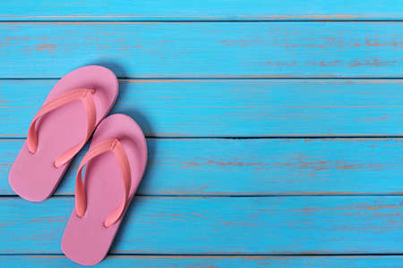 Pink flip flop sandals old summer beach wood background painted blue