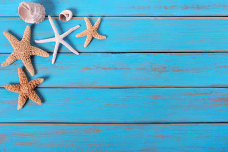 Several starfish old weathered blue beach wood deck background 免版税图像