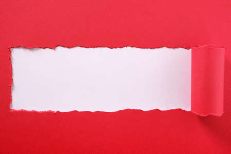 Torn red paper strip curled edge center frame white background
