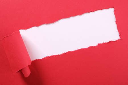 Torn red paper strip curled edge angled diagonal white background Stock fotó