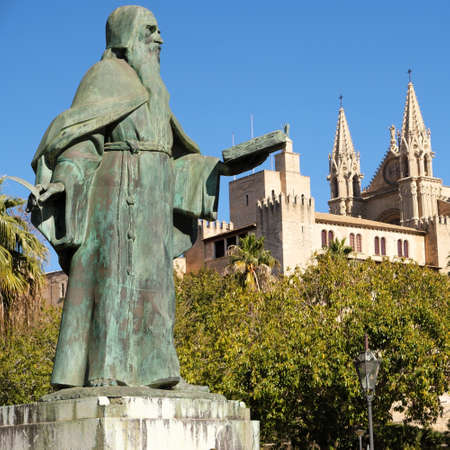 Palma de Mallorca, Spain - March 25, 2019 : side view of the famous gothic cathedral Santa Maria La Seu, the Kings palace Almudaina and statue of Ramon Llull in the foreground