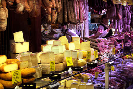Palma Mallorca, Spain - March 20, 2019 : serrano and iberian iberico ham legs, sausage, chorizo and cheese on display for sale in the local farmers indoor market stall shop