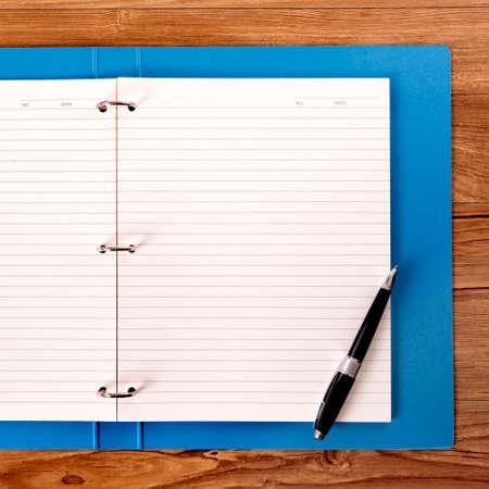 Bureau d'étudiant avec dossier de projet bleu et stylo à bille.