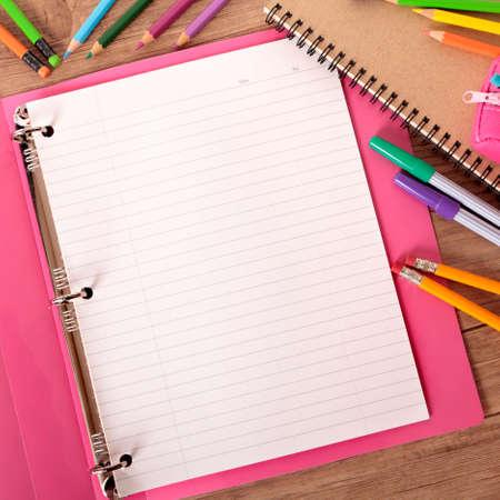 Escritorio de estudiante ocupado con carpeta de proyectos rosa rodeada de bolígrafos, lápices y cuadernos.