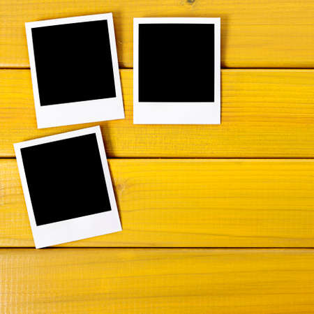 Blank instant photo cards pinned on a wooden background. Space for text. 版權商用圖片