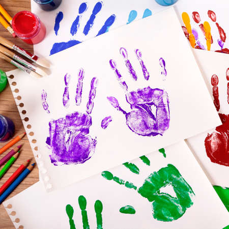 Painted handprints with art and craft equipment on a school table. Archivio Fotografico