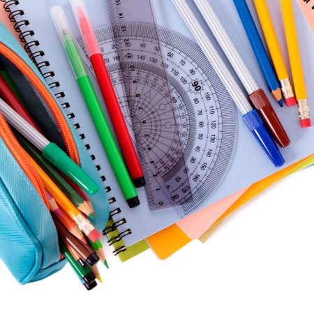 Diverses fournitures scolaires, y compris des cahiers et un étui à crayons isolés sur fond blanc