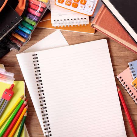 Drukke studentenbureau met opengeslagen notitieboekje, schooltas, tekstboeken en diverse potloden en kleurpotloden.