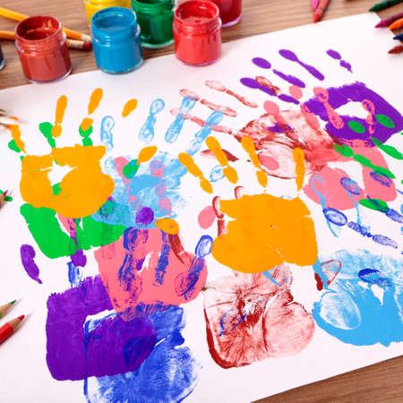 Empreintes de mains peintes avec du matériel d'art et d'artisanat sur une table d'école. Faible profondeur de champ avec une mise au point nette sur les empreintes de mains les plus proches et un arrière-plan flou à distance.