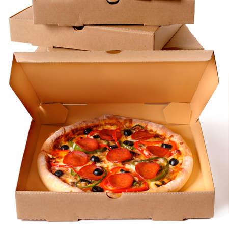 Pizza ai peperoni italiana appena sfornata con una pila di scatole di consegna isolate su uno sfondo bianco.