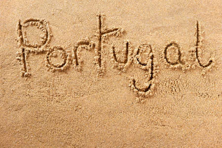Portugal algarve beach word written in sand