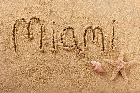 Miami beach word sign message written in sand