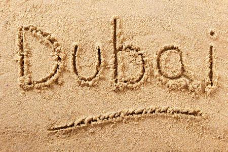 Dubai beach word written in sand