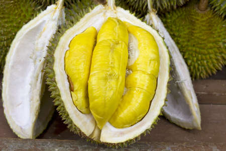 Durian open in display with yellow flesh on fruit stand in tropical country Stock Photo