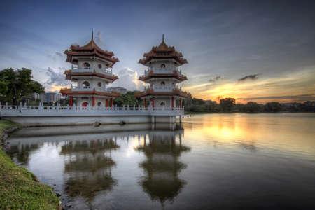 シンガポールの中国人の庭湖で夕焼けでツイン塔 写真素材