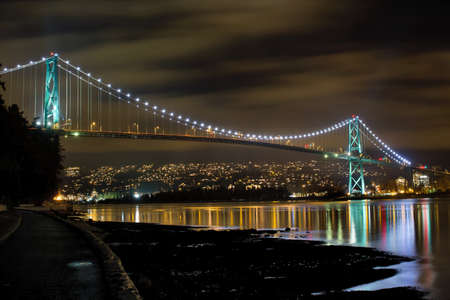 port stanley: Lions Gate Bridge Over English Bay in Vancouver BC Canada at Night Stock Photo