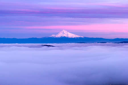 Mt Hood and Low Foggy Clouds over City of Portland in Oregon at Sunset