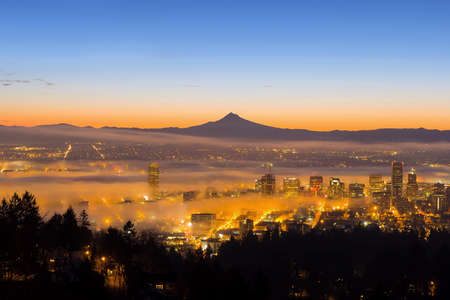 Portland Oregon downtown cityscape with Silhouette of Mount Hood covered in Low Fog during Sunrise
