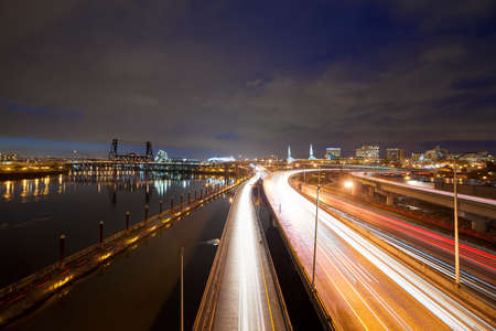 eastbank: Freeway traffic light trails along Willamette River with city of Portland Oregon skyline at night