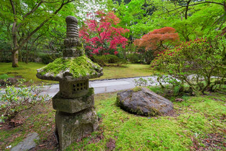 Old Stone Lantern In Japanese Garden With Trees And Shrubs Landscape In  Spring Season Stock Photo