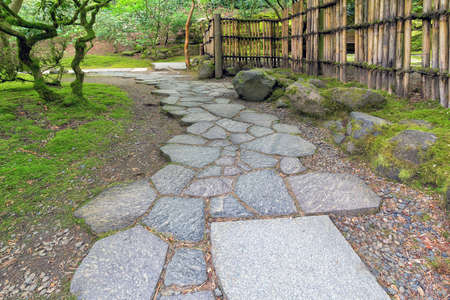 garden path: Stone Path Walkway with Bamboo Fence at Japanese Garden Stock Photo
