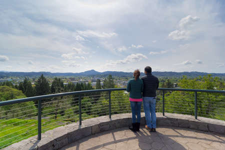 eugene: Couple at top of Skinner Butte Park viewing deck enjoying view of downtown Eugene Oregon on a beautiful day