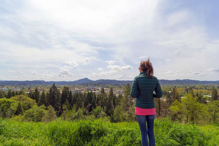 eugene: Woman at top of Skinner Butte Park enjoying view of downtown Eugene Oregon on a beautiful day