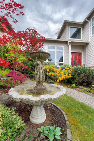 residential neighborhood: Stone Water Fountain on Landscaped Frontyard of House in Residential Neighborhood in the Suburbs