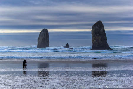 oregon coast: Photographer capturing waves by Haystack Rock at Cannon Beach along the Oregon Coast