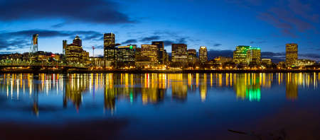 Portland Oregon downtown city skylinw by Hawthorne Bridge along Willamette River at evening blue hour panorama Stock Photo