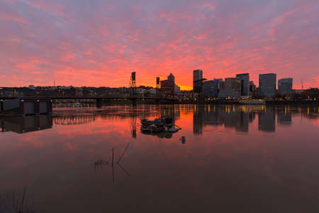 Fiery sunset over Portland Oregon skyline along Willamette River by Hawthorne Bridge Stock Photo