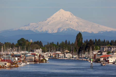 Mount Hood over floating homes boat houses along Columbia River Stock Photo