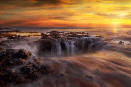 Thors Well at Cooks Chasm by Cape Perpetua on the Oregon Coast during a fiery unset 版權商用圖片