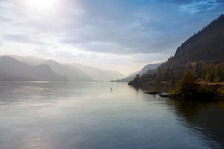 Paddle Boarding on the Columbia River Gorge in the hazy afternoon Stock Photo