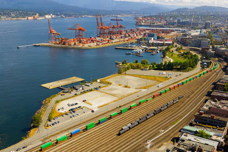 Port of Vancouver British Columbia Canada with containers shipyard cranes and train railroad tracks transportation 写真素材
