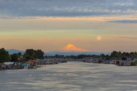 Full moonrise over Mount Hood and floating boat houses along Columbia River