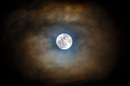 Full moon visible with parting of the clouds in the night sky Banco de Imagens - 83254173