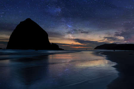 Haystack Rock at Cannon Beach under starry night sky in Oregon Coast