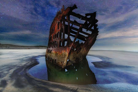 Peter Iredale Shipwreck at low tide on the Oregon Coast under a starry night sky