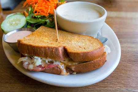 Corned Beef Sandwich with Swiss Cheese Sauerkraut Salad and cup of Clam Chowder closeup macro