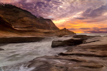 Crashing waves at Cape Kiwanda in Pacific City Oregon Coast during sunset Stock Photo