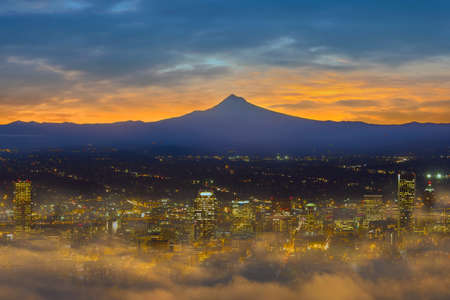 Foggy morning at Portland Oregon downtown city skyline with Mount Hood silhouette at dawn